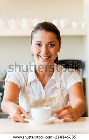 Enjoy fresh coffee! Beautiful young woman in apron serving coffee and smiling while standing in coffee shop - stock photo
