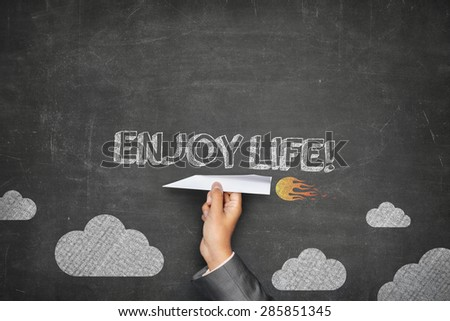 Enjoy life concept on black blackboard with businessman hand holding paper plane - stock photo