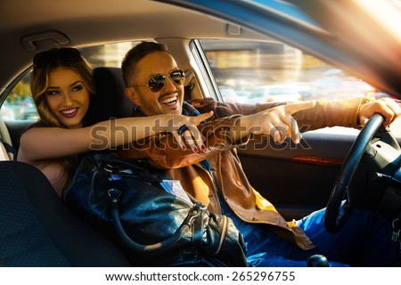 Enjoy life fun couple driving car at high speed and point fingers forward. Inside photo - stock photo
