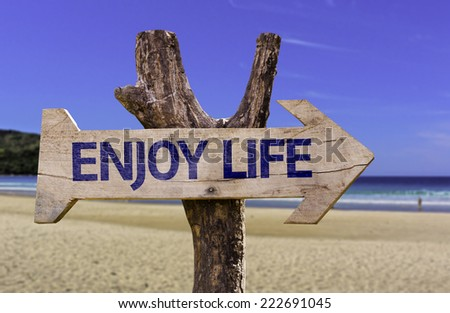 Enjoy Life wooden sign with a beach on background - stock photo