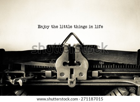 Enjoy little things in life inspirational message typed on vintage typewriter  - stock photo