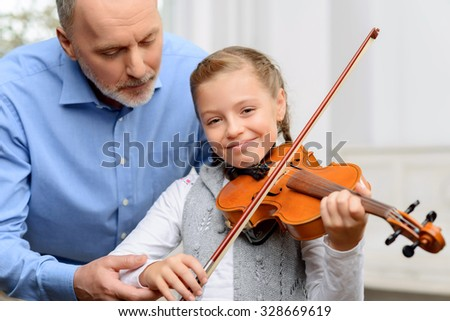 Enjoy music. Cheerful smiling little girl holding fiddle bow while learning to play violin with her grandfather - stock photo