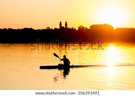 Enjoy sunset - man kayaking on lake - stock photo