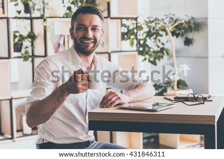 Enjoy the best coffee in town! Cheerful young man holding cup of coffee and looking at camera with smile while sitting in cafe - stock photo