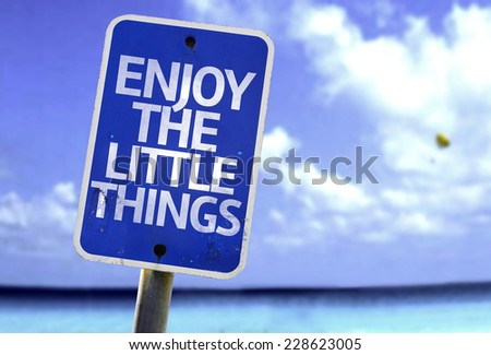 Enjoy the Little Things sign with a beach on background