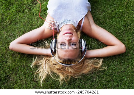enjoy the music, young blond happy woman in headphones on the grass - stock photo
