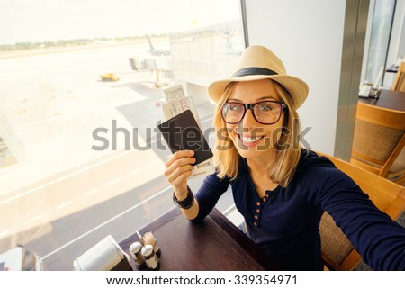 Enjoy traveling! Vacation Selfie. Beautiful young woman in hat taking selfie while waiting for boarding in the airport. - stock photo