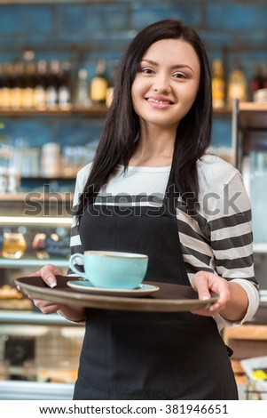 Enjoy your drink. Beautiful young waitress holding out a tray with a cup of coffee smiling joyfully - stock photo