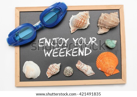 Enjoy Your Weekend text on chalk board with swimming goggle and shell - vacation and business concept - stock photo