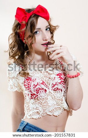 enjoying a bar of chocolate funny sexy pinup girl blond young beautiful woman having fun posing over white wall copy space background portrait picture - stock photo