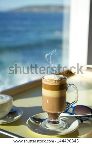 Enjoying a caf�© mocha with a beautiful view over the sea - stock photo