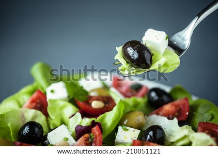 Enjoying a healthy Greek salad of feta cheese, olives tomatoes and leafy green with a fork suspended above the plate with lettuce, feta and olive on it - stock photo