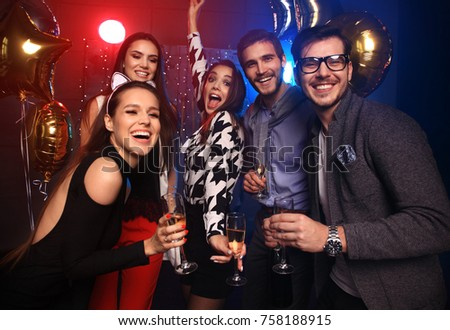 Enjoying amazing party. Group of beautiful young people dancing with champagne flutes and looking happy. New year's party