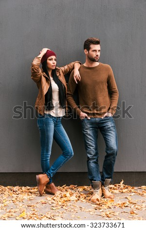 Enjoying autumn style. Beautiful young couple bonding to each other and looking away while leaning at the grey wall with fallen leaves laying around them - stock photo