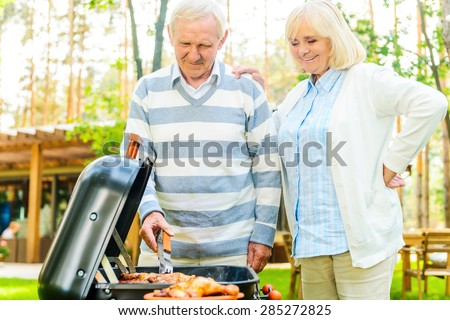 Enjoying barbeque together. Happy senior couple barbecuing meat on the grill while standing at the back yard of their house - stock photo