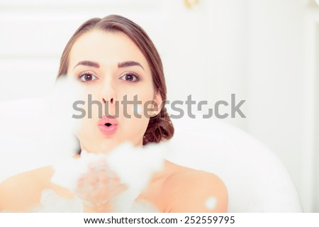 Enjoying bubble bath. Closeup image of playful attractive young woman blowing an air kiss to camera and smiling while enjoying luxurious bath - stock photo