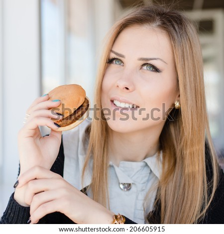 enjoying burger: eating delicious hamburger beautiful young woman cute blond girl having fun in restaurant or coffee shop happy smiling & looking at camera on copy space background closeup portrait - stock photo
