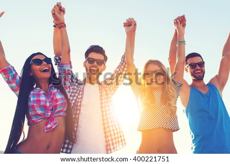 Enjoying carefree time together. Low angle view of four cheerful young people holding hands and keeping arms raised while standing against sky - stock photo