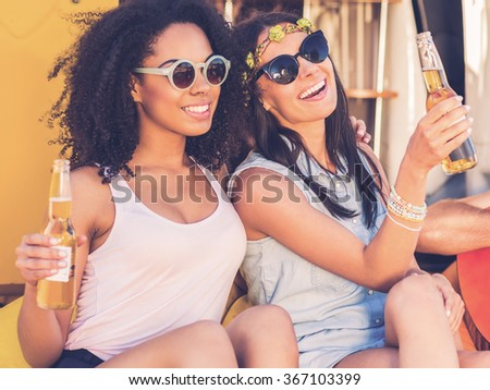 Enjoying carefree time. Two cheerful young women holding bottles with beer and smiling while while sitting outdoors together - stock photo