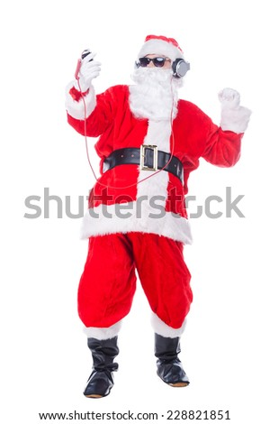 Enjoying Christmas music. Full length of Santa Claus in sunglasses and headphones listening to MP3 Player and gesturing while standing against white background - stock photo