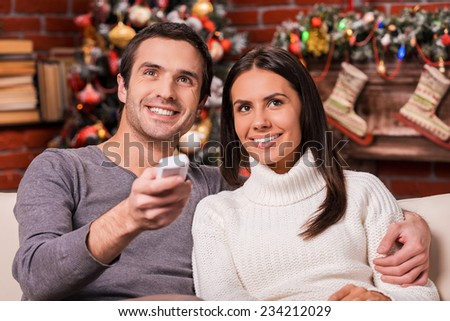 Enjoying Christmas shows together. Beautiful young loving couple bonding to each other and smiling while watching TV together with Christmas Tree in the background