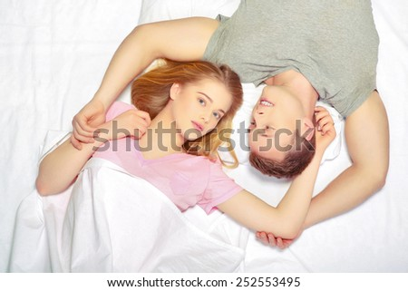 Enjoying closeness. Top view of beautiful young loving couple lying together in bed and looking at camera - stock photo