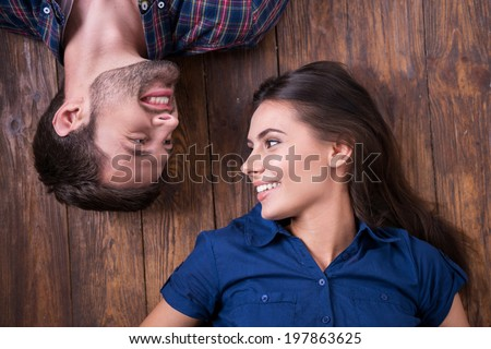 Enjoying closeness. Top view of beautiful young loving couple lying together on the hardwood floor and looking at each other  - stock photo
