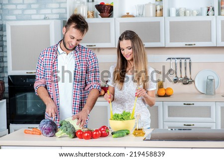 Enjoying cooking together. Young and beautiful couple in love looking at each other while preparing dinner with vegetables in the kitchen. - stock photo
