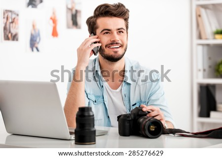 Enjoying creative work. Happy young man talking on the mobile phone and smiling while sitting at his working place and holding digital camera - stock photo