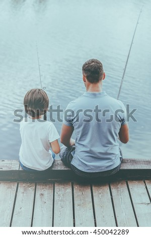 Enjoying day fishing. Rear view of father and son fishing while sitting on quayside together - stock photo