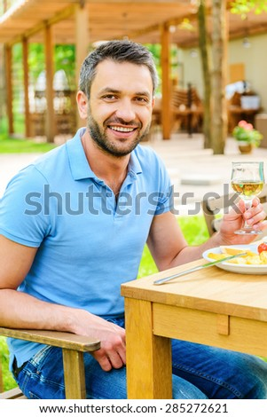 Enjoying dinner outdoors. Happy young man holding glass with wine and smiling while sitting at the dining table outdoors  - stock photo