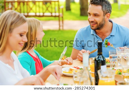 Enjoying dinner together. Happy family enjoying meal together while sitting at the dining table outdoors  - stock photo