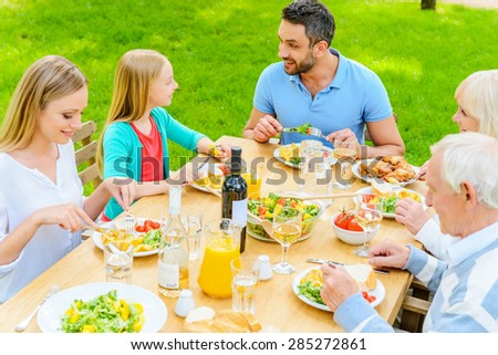 Enjoying dinner together. Top view of happy family of five people communicating and enjoying meal together while sitting at the dining table outdoors  - stock photo