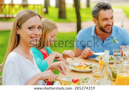 Enjoying dinner with the nearest. Happy family enjoying meal together while woman looking at camera and smiling  - stock photo
