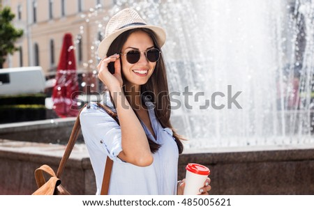 Enjoying every minute of summer. Beautiful young smiling woman in sunglasses looking away while walking by the street with coffee.