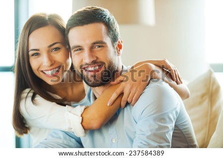 Enjoying every minute together. Beautiful young loving couple sitting together on the couch while woman embracing her boyfriend and smiling  - stock photo