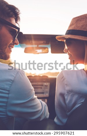 Enjoying every minute together. Rear view of happy young couple looking at each other while sitting inside of their convertible  - stock photo