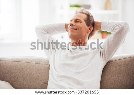 Enjoying free time at home. Cheerful mature man holding hands behind head and looking relaxed while sitting on the couch at home - stock photo