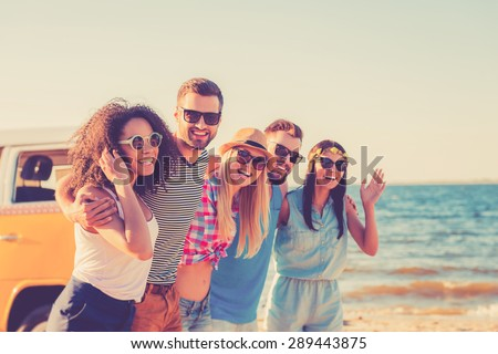 Enjoying freedom. Group of cheerful young people embracing and looking at camera while walking along the beach  - stock photo