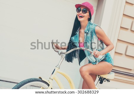 Enjoying freedom. Low angle view of cheerful young woman smiling and looking forward while riding on bicycle outdoors - stock photo