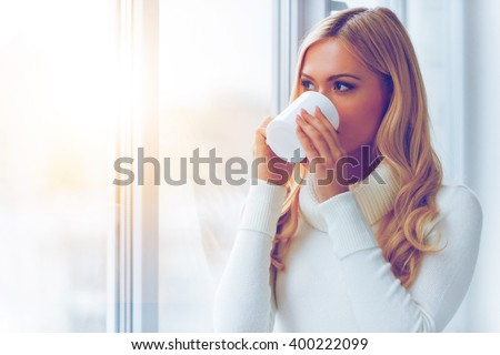 Enjoying fresh coffee. Beautiful young woman in white sweater drinking coffee and looking through a window