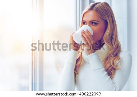 Enjoying fresh coffee. Beautiful young woman in white sweater drinking coffee and looking through a window  - stock photo