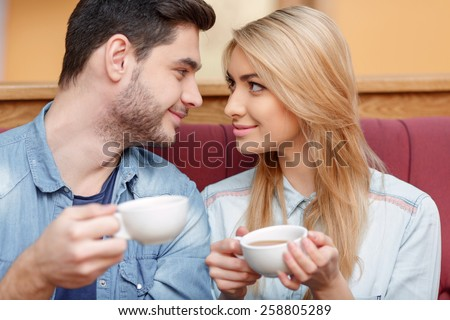 Enjoying fresh coffee together. Closeup of beautiful young couple looking at each other and smiling while enjoying coffee in cafe together - stock photo