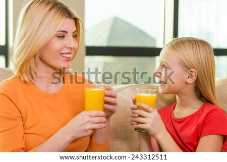 Enjoying fresh juice. Happy mother and daughter holding glasses with orange juice and looking at each other with smile while sitting on the couch together  - stock photo