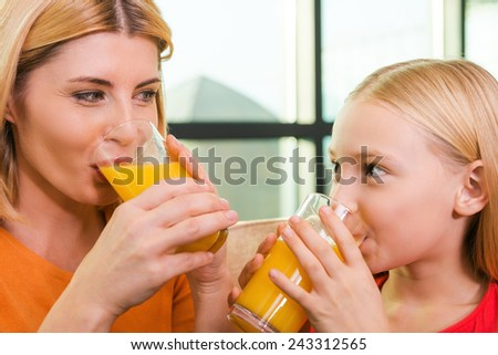 Enjoying fresh juice together. Cheerful mother and daughter drinking orange juice and looking at each other with smile while sitting on the couch together  - stock photo