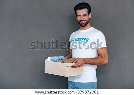 Enjoying giving back to community. Confident young man in volunteer t-shirt holding donation box in his hands and looking at camera with smile while standing against grey background
