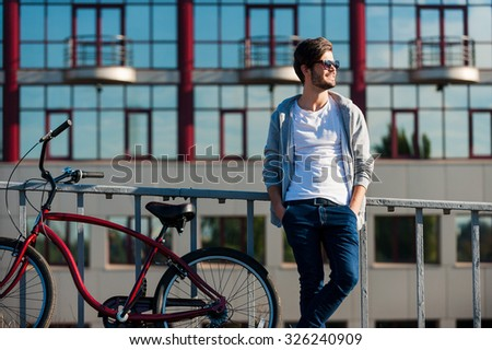 Enjoying good day. Handsome young smiling man holding hands in pockets and looking away while standing near his bicycle outdoors - stock photo