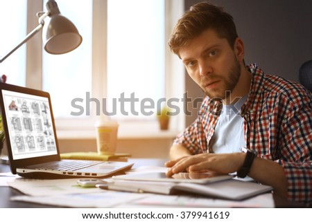 Enjoying good working day. Confident young man working on laptop while sitting at his working place in office - stock photo