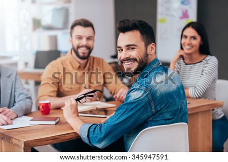 Enjoying good working day together. Group of confident business people in smart casual wear sitting at the table and smiling - stock photo