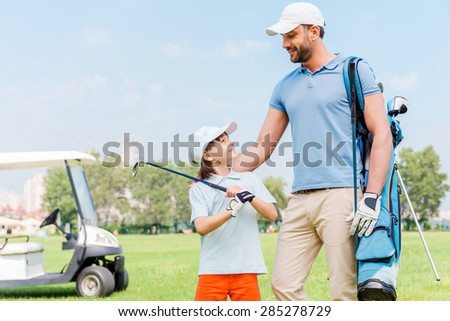 Enjoying great game together. Smiling young man and his son looking at each other while standing on the golf course - stock photo